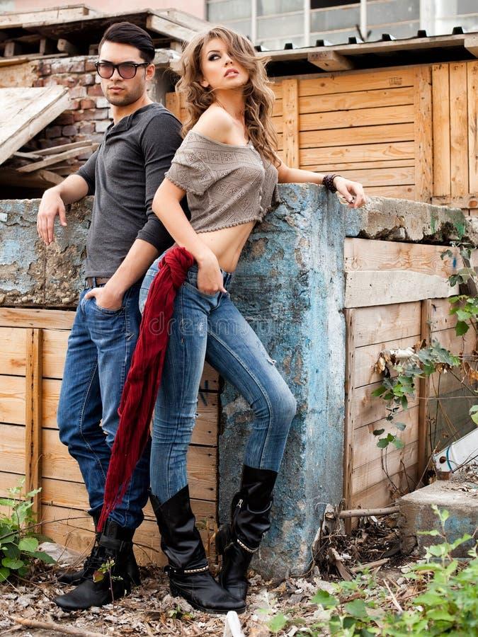 Sexy modieus paar die jeans dramatisch stellen dragen stock afbeeldingen