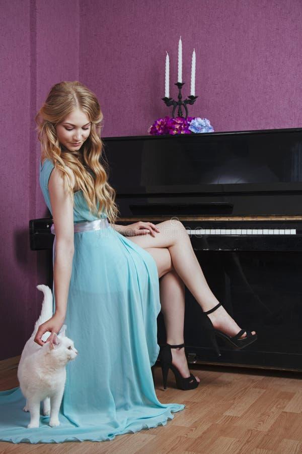Sexy mooi blondemeisje in kleding het spelen piano met een kat stock afbeelding