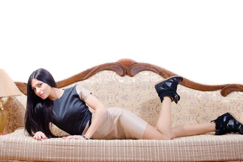 Sexy mooie donkerbruine jonge dame die op het bed in de zwarte rok liggen die van het tennisschoenenleer de camera bekijken royalty-vrije stock afbeelding