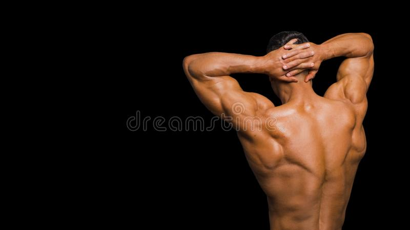 Muscle man. Back view. Isolated on dark. Muscle man. Back view. Isolated on dark stock photography