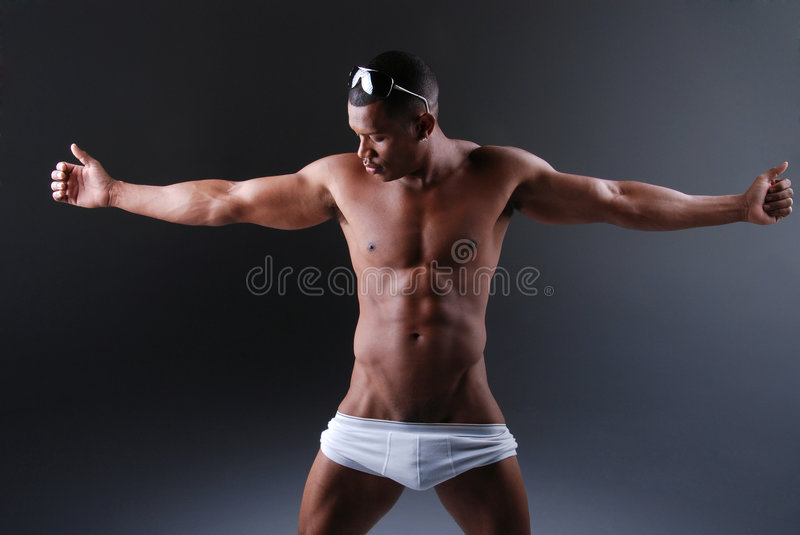 Muscular man. Muscular African American man wearing white underwear holding both arms out to the side stock photo
