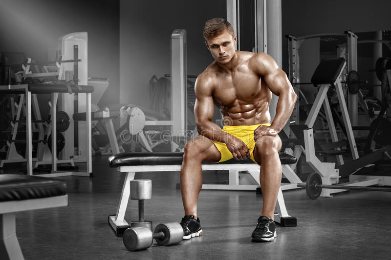 muscular man in gym, shaped abdominal. Strong male naked torso abs, working out stock photography