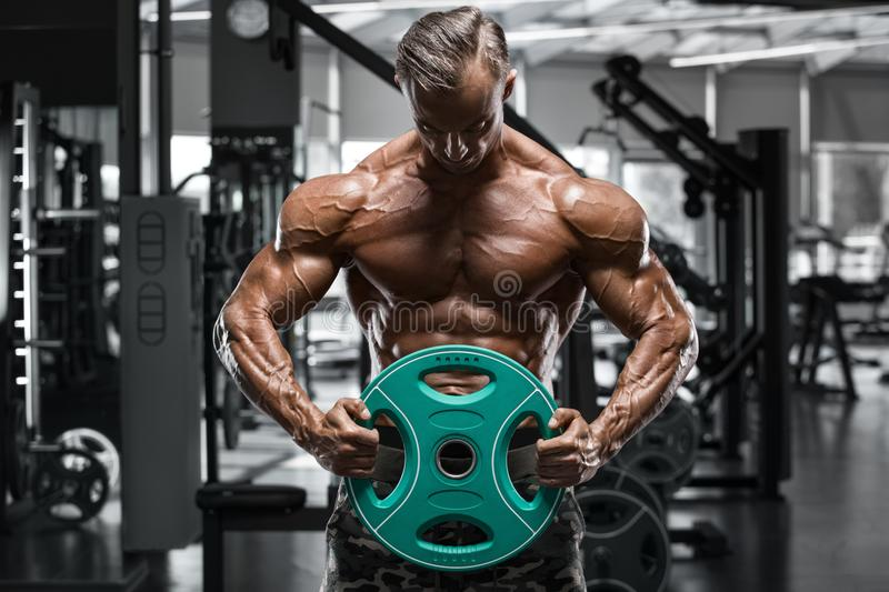 muscular man in gym, shaped abdominal. Strong male naked torso abs, working out royalty free stock image