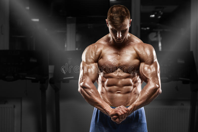 muscular man posing in gym, shaped abdominal, showing muscles. Strong male naked torso abs, working out royalty free stock photos