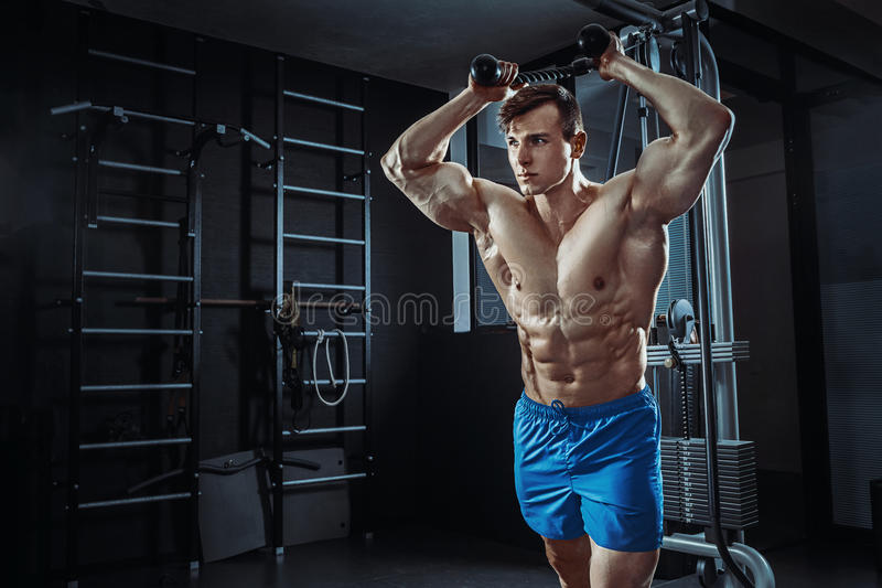 Muscular man posing in gym, shaped abdominal. Strong male naked torso abs, working out. Athlete in blue shorts stock photography