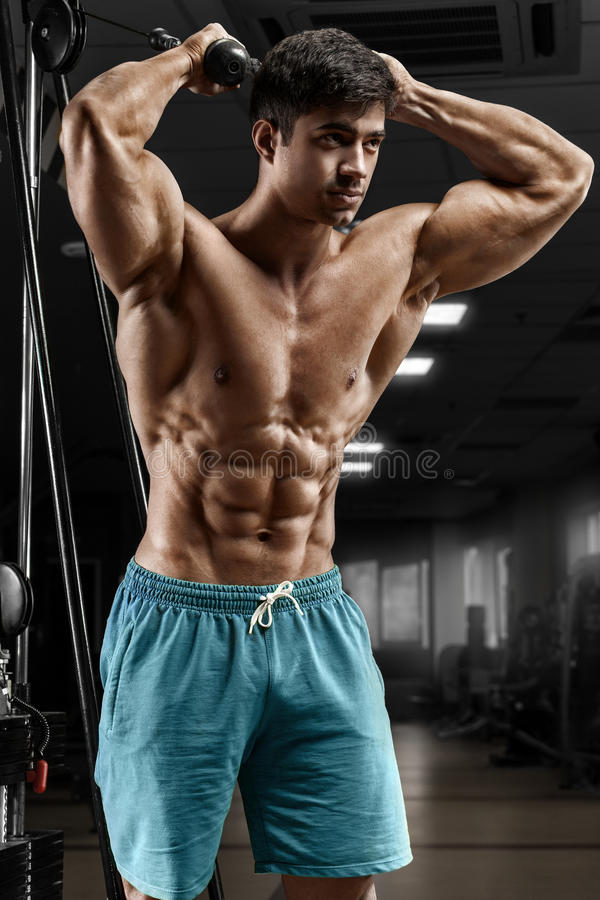 Muscular man working out in gym doing exercises, strong male naked torso abs.  stock image