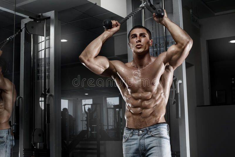 muscular man working out in gym, shaped abdominal. Strong male naked torso abs stock photo