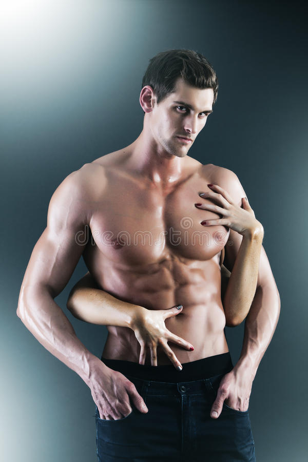 Muscular naked man and female hands. Holding his chest royalty free stock photography