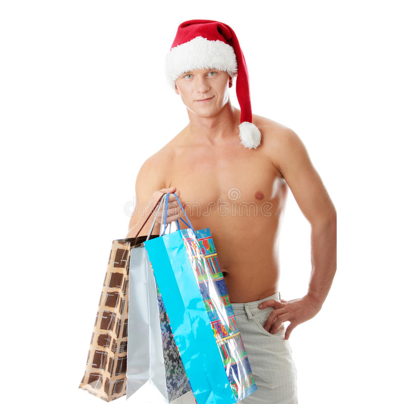 muscular shirtless man in Santa Claus hat royalty free stock images