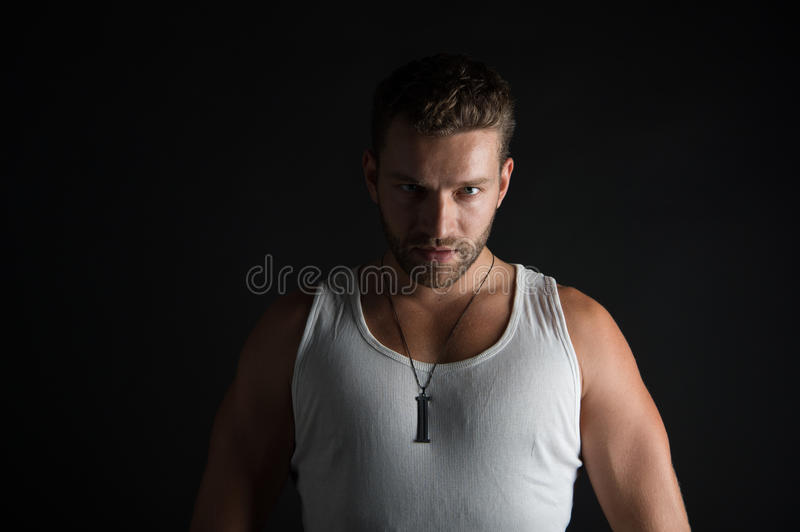 Muscular young man. Young handsome bearded man macho with muscular hands and beard on serious face in white vest posing in studio on black background stock photography