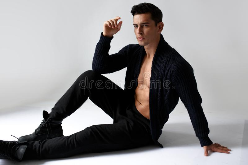 A sexy, muscular young man model, on naked torso in black, sitting in studio,  on white background. stock photos