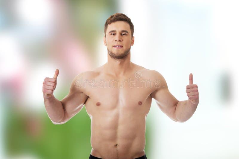 Sexy muskulöser Mann, der sich Daumen zeigt stockfoto