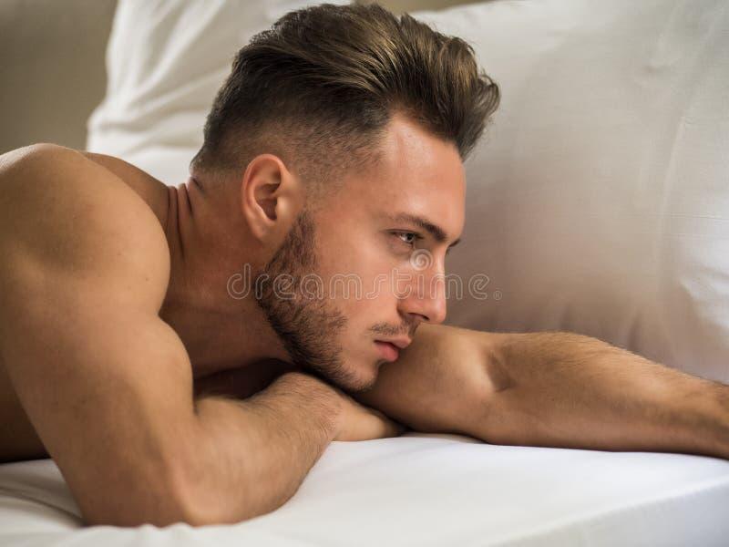 Sexy naakte spier jonge mens op bed stock fotografie