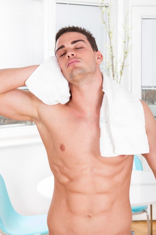 Sexy nackter muskulöser Mann mit dem trocknenden Haar des weißen Tuches lizenzfreie stockbilder