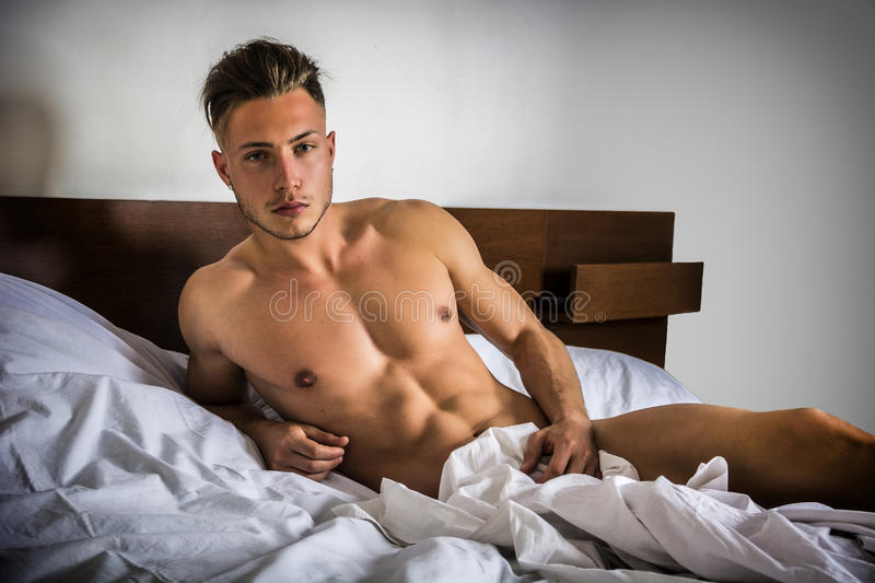 Naked young man on bed. Totally naked young man with muscular body on bed looking away stock image