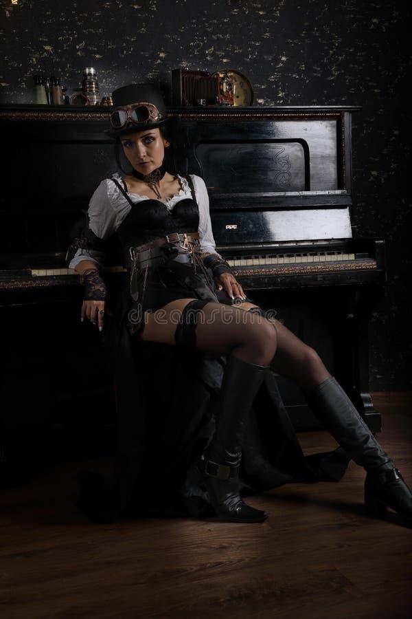 Sexy nettes steampunk Mädchen, das nahe bei dem Klavier sitzt stockfotografie