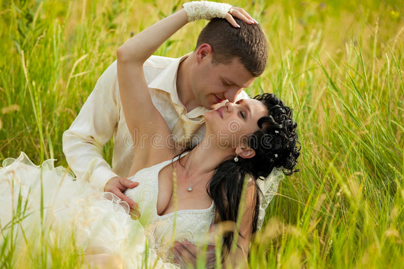 newly-married couple lie on green grass royalty free stock photography