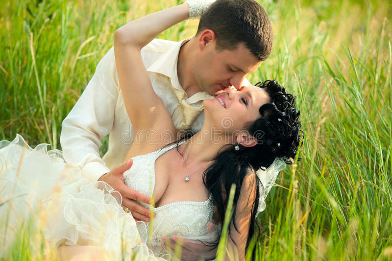 newly-married couple lie on green grass stock images