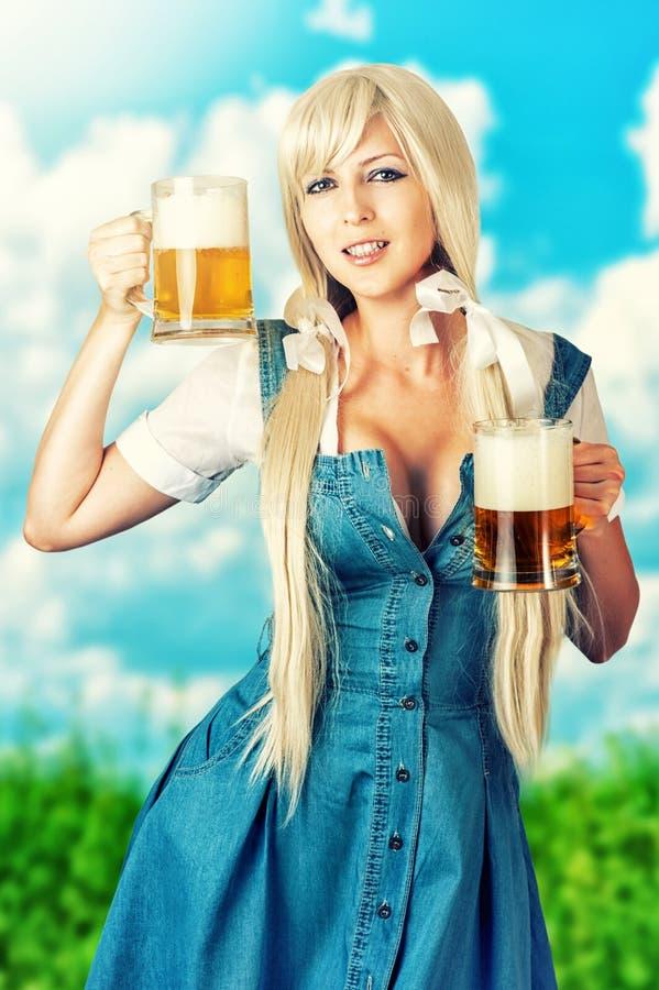 Sexy oktoberfest Mädchen, das zwei Bierkrüge hält stockfoto