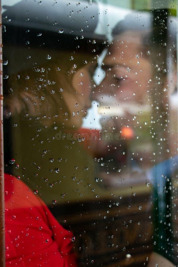 Sexy paar die en elkaar passionately in telefoondoos kussen houden stock foto's