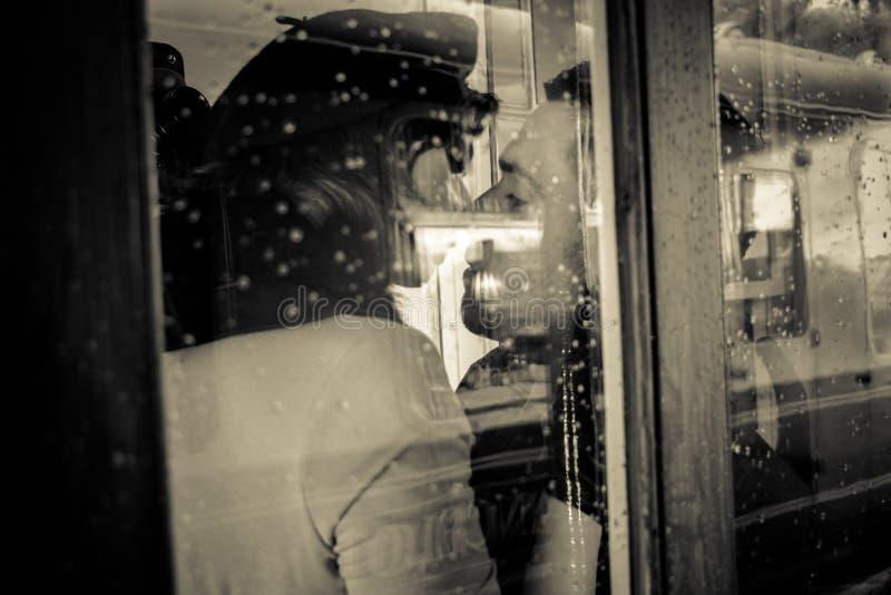 Sexy paar die en elkaar passionately in telefoondoos kussen houden stock afbeeldingen