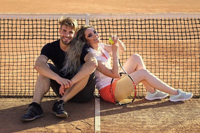 Sexy Paar Het gelukkige paar in liefde zit bij tennis netto op hof royalty-vrije stock foto's