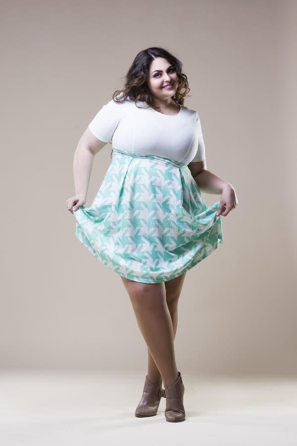 Sexy più il modello di moda in abbigliamento casual, donna grassa sul fondo beige dello studio, ente femminile di peso eccessivo  fotografia stock libera da diritti
