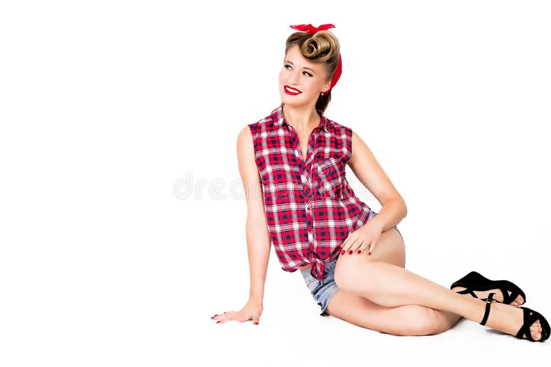 pin-up girl in shorts and high heels sitting on a floor over white background. Beauty, fashion. Full length portrait. royalty free stock images