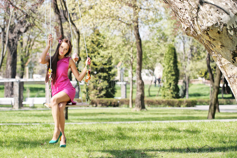 pink purple dress lady on a swing royalty free stock photos