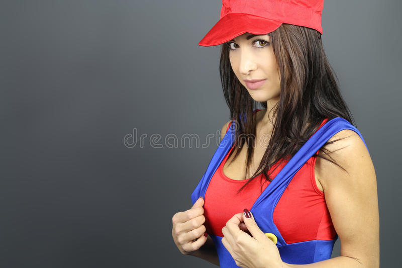 Plumber. Woman dressed in plumber over a gray background royalty free stock images