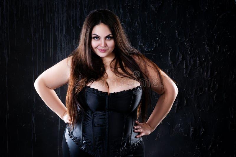 Sexy plus groottemodel in zwart korset, vette vrouw met grote natuurlijke borsten op donkere achtergrond, lichaams positief conce stock afbeeldingen