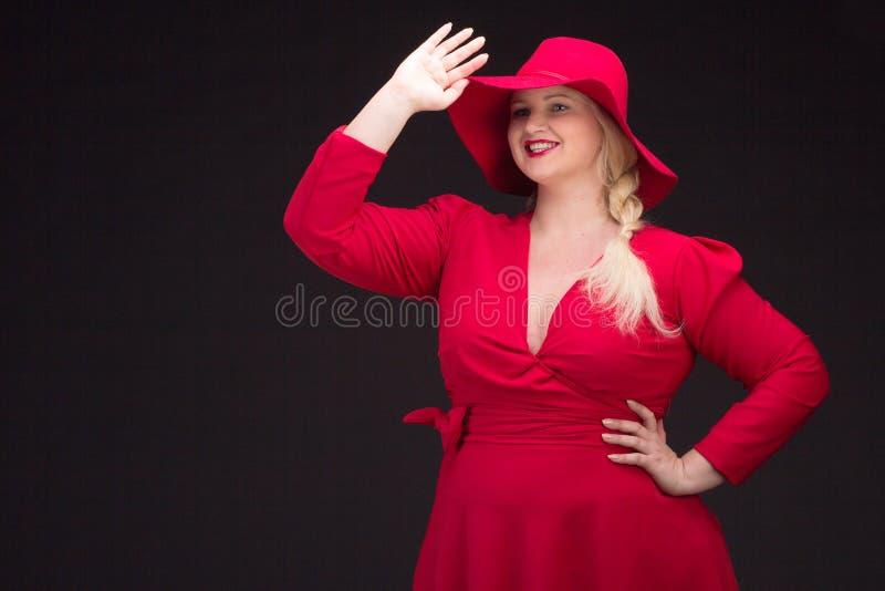 Sexy plus groottevrouw in rode hoed met rode lippen royalty-vrije stock afbeelding