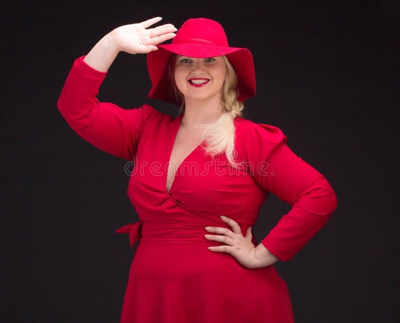 Sexy plus groottevrouw in rode hoed met rode lippen stock fotografie