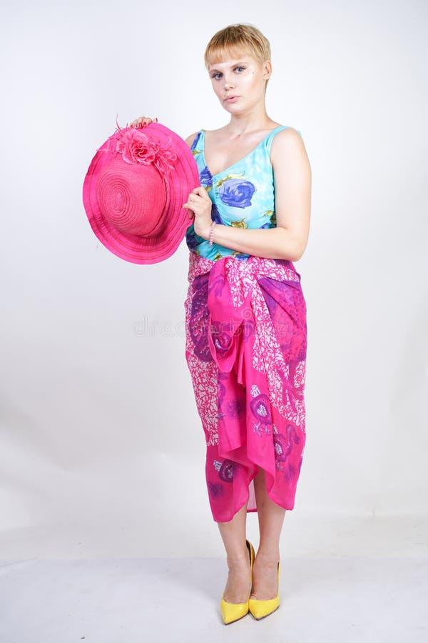 Sexy Plusgrößenmädchen in einem blauen Badeanzug, in einem pinkfarbenen Hut mit Rand und in einem modischen hellen pareo steht au stockfotografie