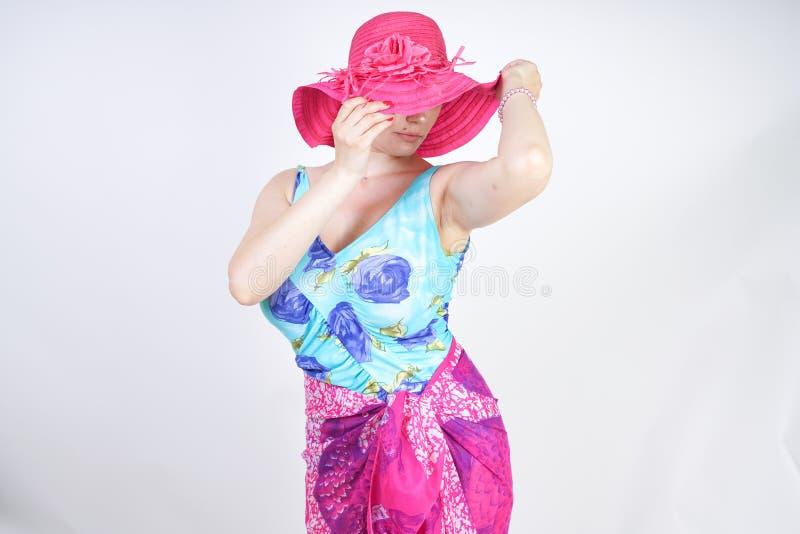 Sexy Plusgrößenmädchen in einem blauen Badeanzug, in einem pinkfarbenen Hut mit Rand und in einem modischen hellen pareo steht au stockbild