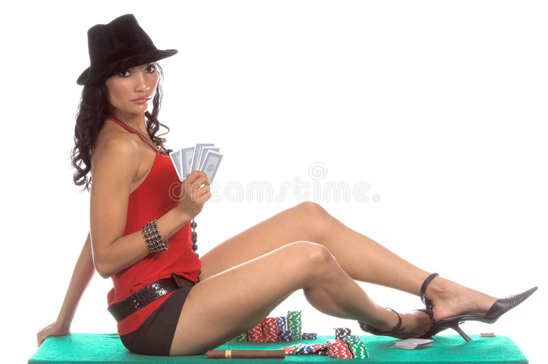 Poker Player. Woman in a low cut red blouse, black hot pants and black suede fedora hat playing Texas Hold 'um poker and smoking a big cigar Generic no label stock photo