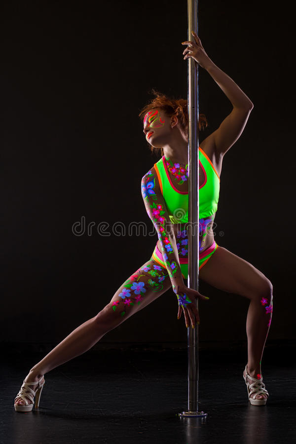 Pole dancer with glowing patterns on her body. Beautiful pole dancer with glowing patterns on her body stock photo