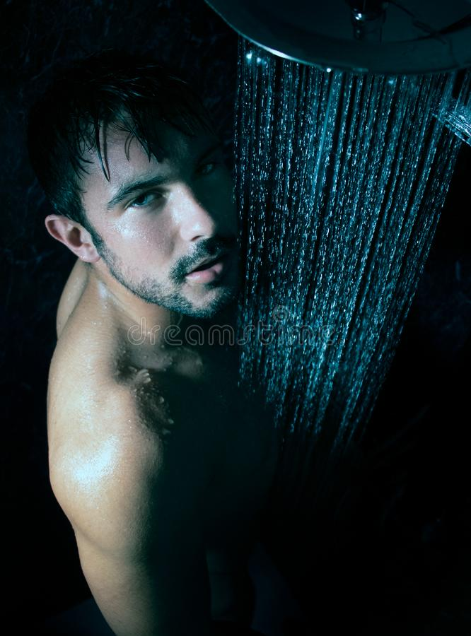 Sexy portrait of handsome naked man with beard and blue eyes under a rainfall shower looking at camera. Sexy portrait of handsome naked man with beard and blue stock photography