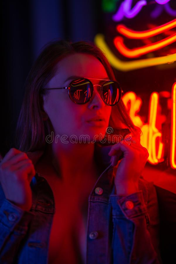 Sexy portrait of a young girl with an open bust in sunglasses and with in the night city, with creative light on the background of. Neon lamps.Night clubs royalty free stock images