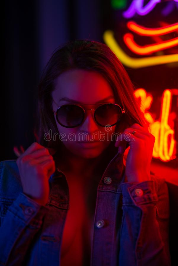 Sexy portrait of a young girl with an open bust in sunglasses and with in the night city, with creative light on the background of. Neon lamps.Night clubs stock images