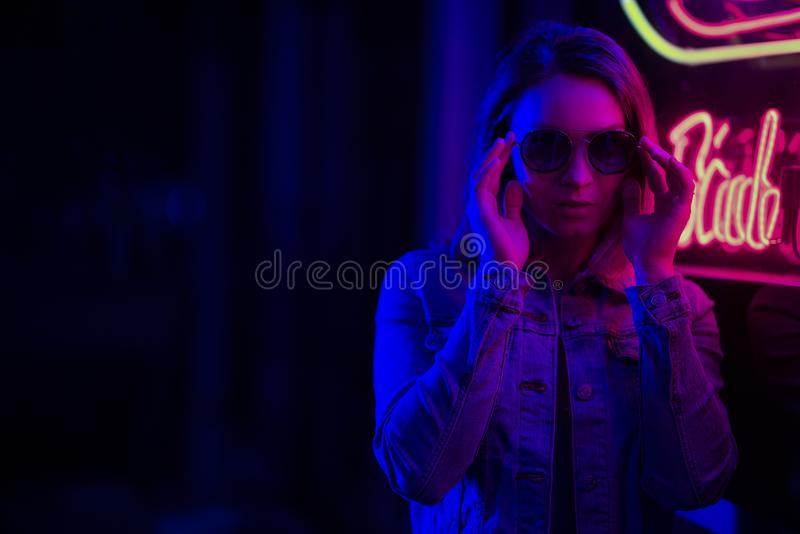 Sexy portrait of a young girl with an open bust in sunglasses and with in the night city, red-blue light of neon lamps. Night. Clubs, parties, strip business royalty free stock photo