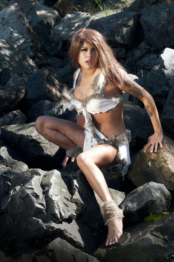Prehistoric Woman. Model dressed as cave woman in animal fur and skins royalty free stock images