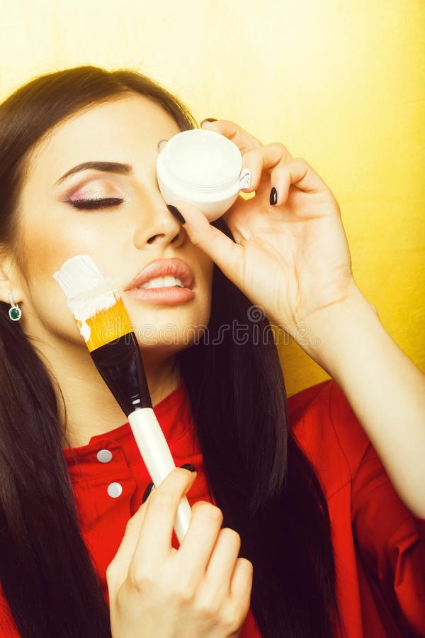 pretty brunette woman face with artist or makeup brush stock photography