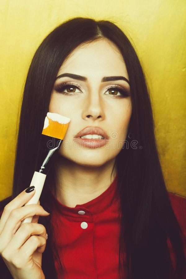 Sexy pretty brunette woman face with artist or makeup brush royalty free stock photo