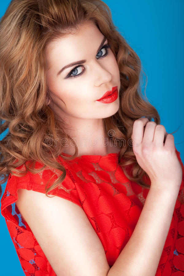 Red Cupids Bow Lips. Beautiful redhead woman with vivid red Cupids bow lips wearing a red dress stock photo