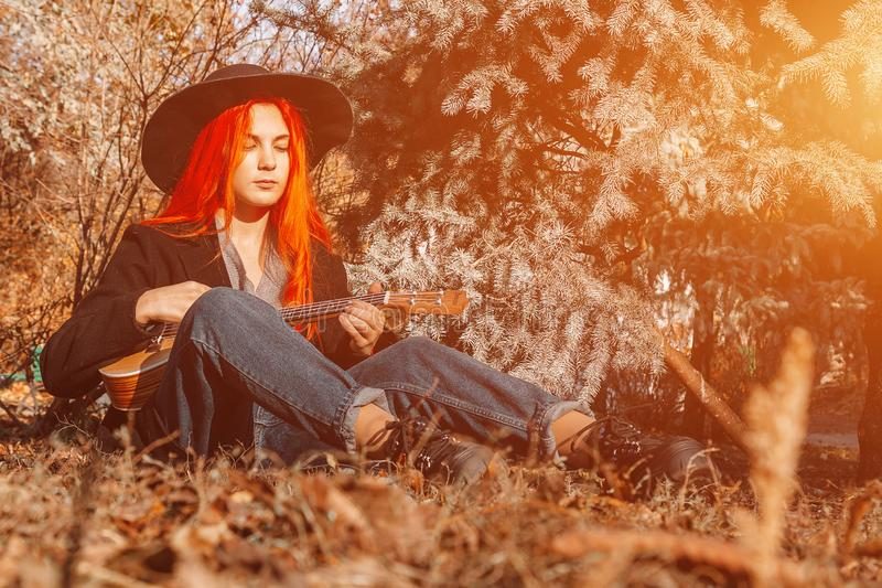 Sexy redhead girl with long hair plays the ukulele. Perfect woman portrait. Gorgeous strong and thick hair. Deep blue eyes. stock image
