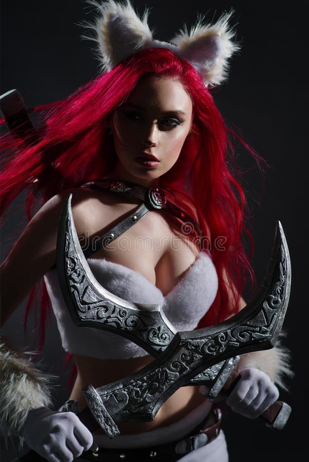 Sexy redhead woman in cosplay costume of warrior cat with swords. Posing on dark background royalty free stock images