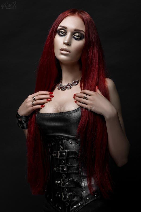 Sexy rode haired vrouw in zwarte leerkleren royalty-vrije stock fotografie