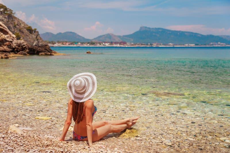 Sexy rug van mooie vrouw in bikini en creatieve hoed op overzeese achtergrond Overzeese kust dichtbij Kemer, Antalya, Turkije royalty-vrije stock fotografie