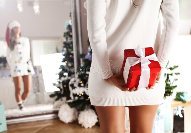 Sexy Sankt-Frau mit einem Weihnachtsgeschenk in ihrer Hand lizenzfreie stockfotos